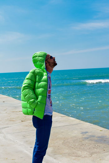 Posing For The Camera People Photography Streetphotography people and places One Mature Man Only Enjoying The Sun Green Color Blue Sky Beautiful Nature Sunnyday☀️ Water Wave Sea Beach Sand Standing Full Length Sky Horizon Over Water Beach Holiday Shore Hiker Sandy Beach Calm Wearing