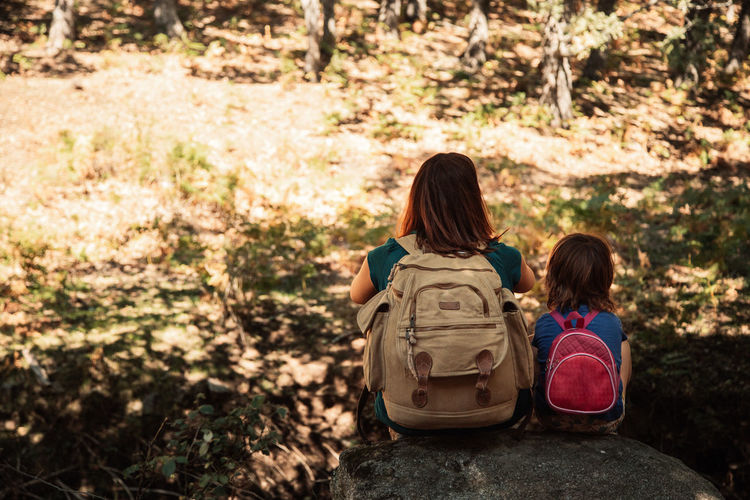 Rear view of mother and daughter with backpacks sitting on rocks in forest