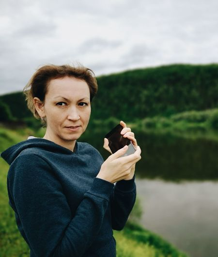 Portrait of woman holding mobile phone while standing on field