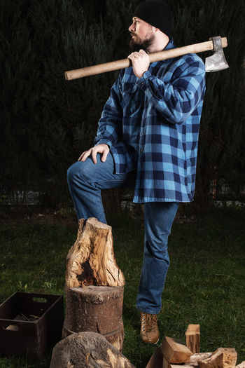 Lumberjack holding axe while standing by log at forest