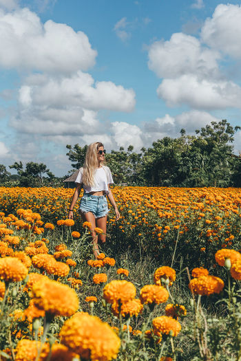 Woman standing by yellow flowers on field against sky