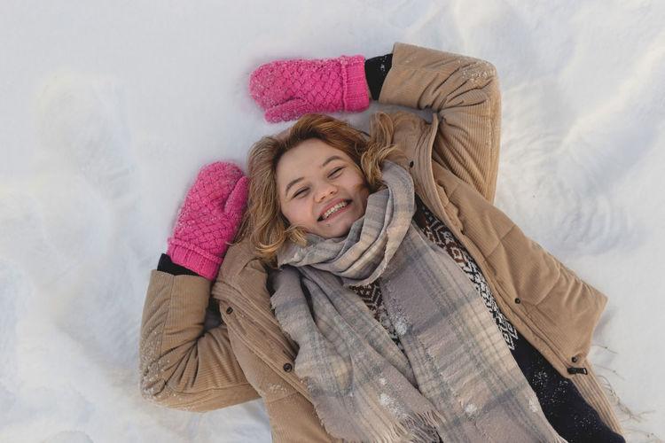 Blonde caucasian girl with pink mittens lies on the snow enjoying winter. happy joyful winter