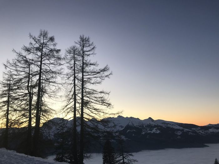 Scenic view of snowcapped mountains against sky at sunset