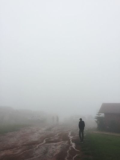 Rear view of man walking on field during foggy weather