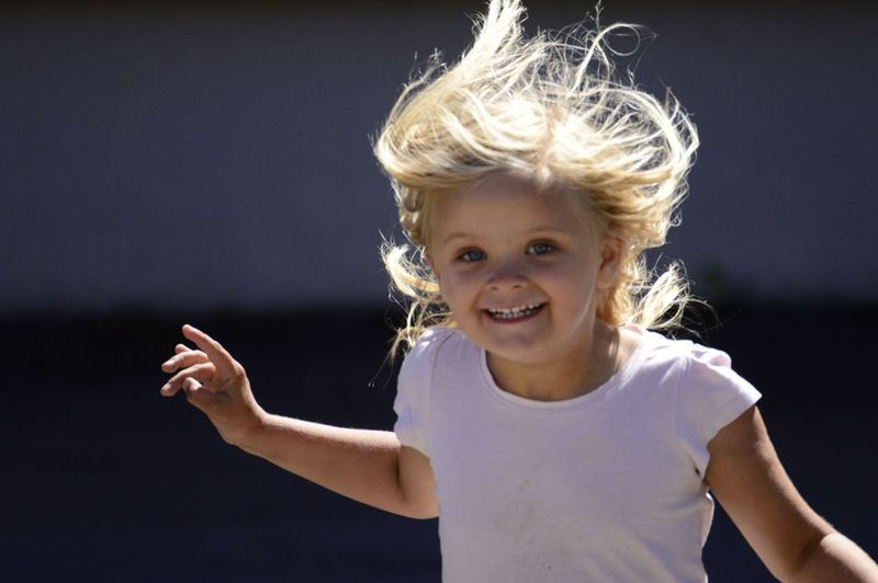 Portrait Of Smiling Girl Running Outdoors