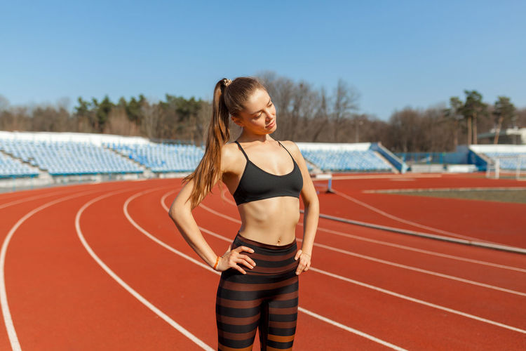 Young woman exercising on running track