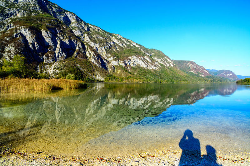 Nature Sky Day Bohinjsko Jezero Water Beauty In Nature Scenics - Nature Mountain Lake Real People Tranquility Non-urban Scene Leisure Activity Tranquil Scene Blue Rear View Reflection Lifestyles One Person Clear Sky Mountain Range Outdoors Looking At View