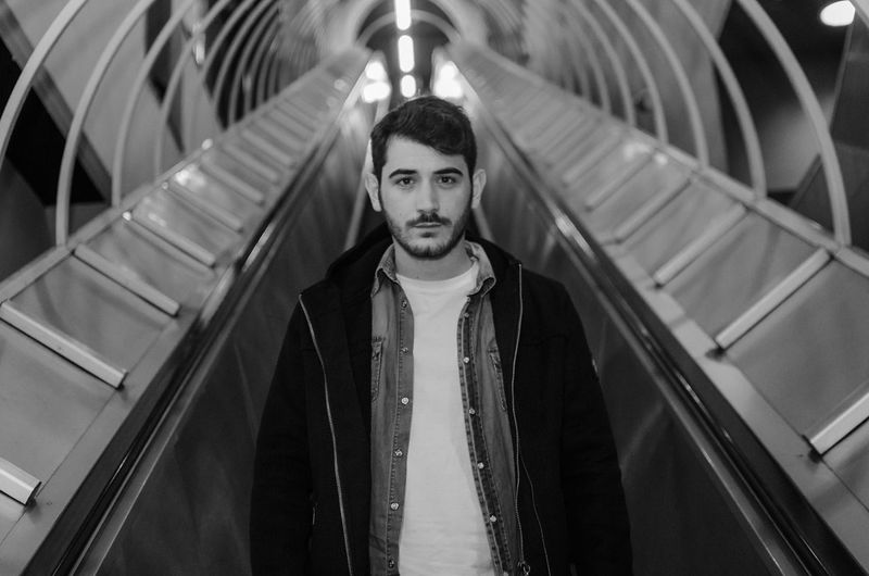 Portrait of young man standing on escalator