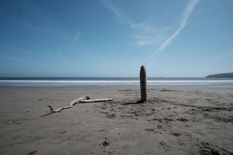 Wooden Post In Sand At Beach Against Sky