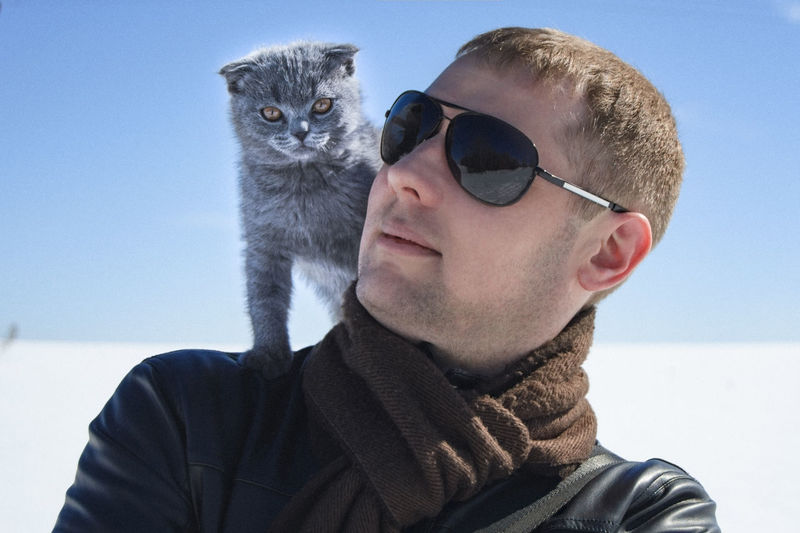 Close-Up Of Man With Cat On Shoulder Against Sky