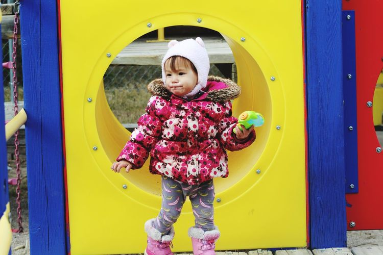 Cute girl looking away while standing in playground