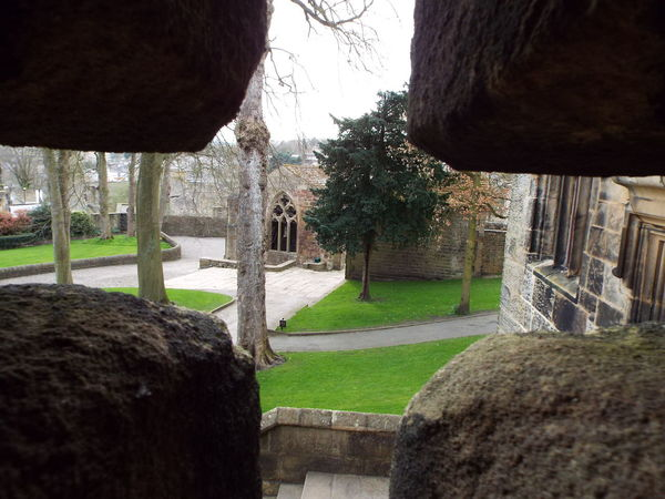 Looking through the cross shaped arrowslit (also referred to as an arrow loop, loophole and balistraria) overlooking the castle's main entrance and the castle's chapel of St. John the Evangelist of which a date of when it was built is not known. The chapel is thought to have been built in the 13th century Arrow Slits Arrowslit Arrowloop Loophole Loop Hole Balistraria Cross Shape Cross Shaped Medieval Castle Medieval Castle Skipton Castle Gatehouse Skipton Castle Gatehouse Main Entrance Entrance Castle Entrance Chapel St John The Evangelist Chapel