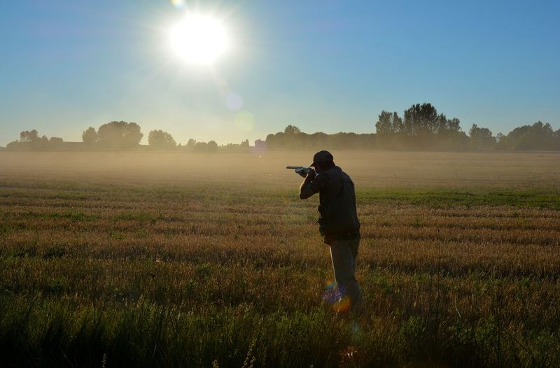 Rear view of man aiming gun while standing on grass against sky