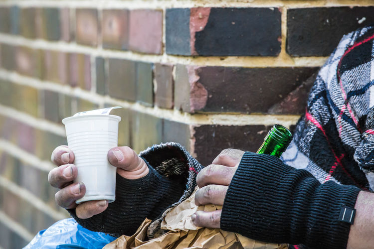 a beggar sits with a bottle of red wine on a street corner Poor  Red Wine Alkohol Beggar Cadge Dirty Drink Homeless Lifestyles Money Needy One Person Street Street Corner