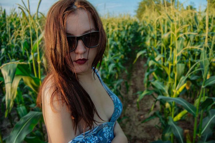 Portrait of seductive woman standing on field