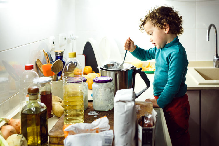Boy having food in kitchen at home