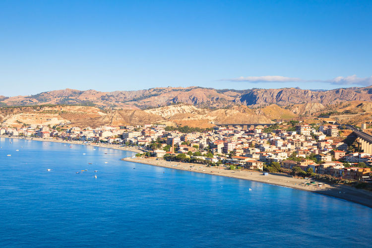 Aerial view of townscape by sea against blue sky