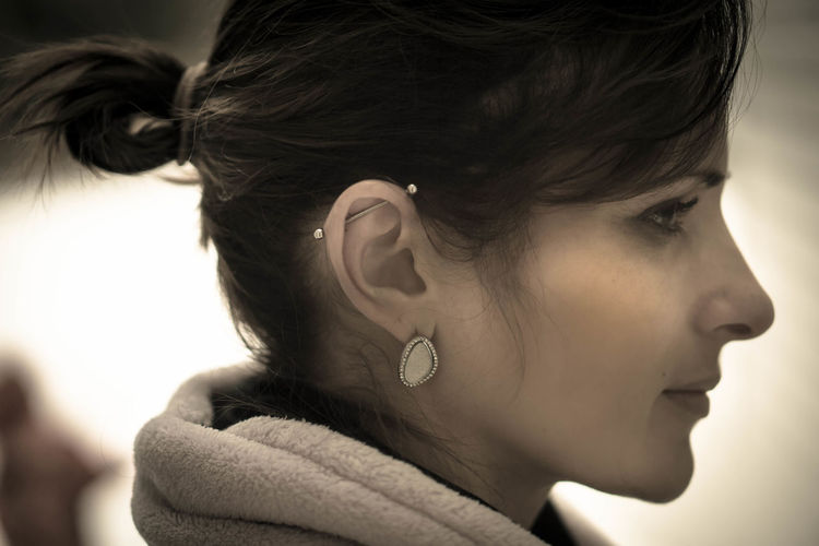 Close-up side view of young woman with pierced ear