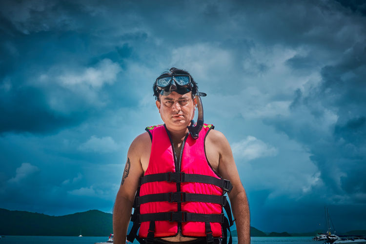 Portrait of man wearing life jacket against sky