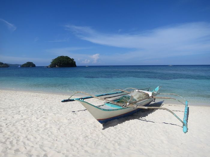 Peaceful by the sea. Seascape Photography Tropical Paradise White Sand Beach Abandoned Beach Lost In The Landscape Fishing Boat Horizon Over Water Nature Nautical Vessel No People Outdoors Outrigger Phillipine Nature Sand Scenics Sea Shore Simple Life Sky Tranquil Scene Tranquility Transportation Water