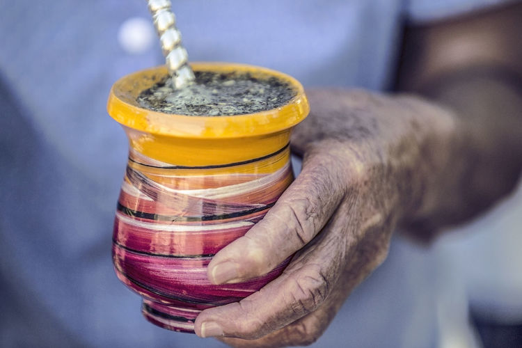 Midsection of person holding yerba mate drink in container