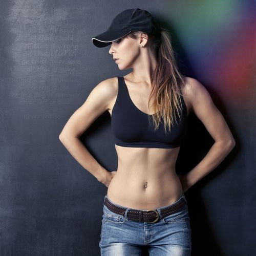 Woman wearing sports bra and cap standing against black wall