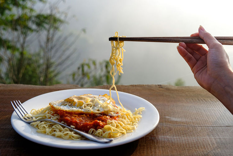 Close-up of hand holding food in plate on table