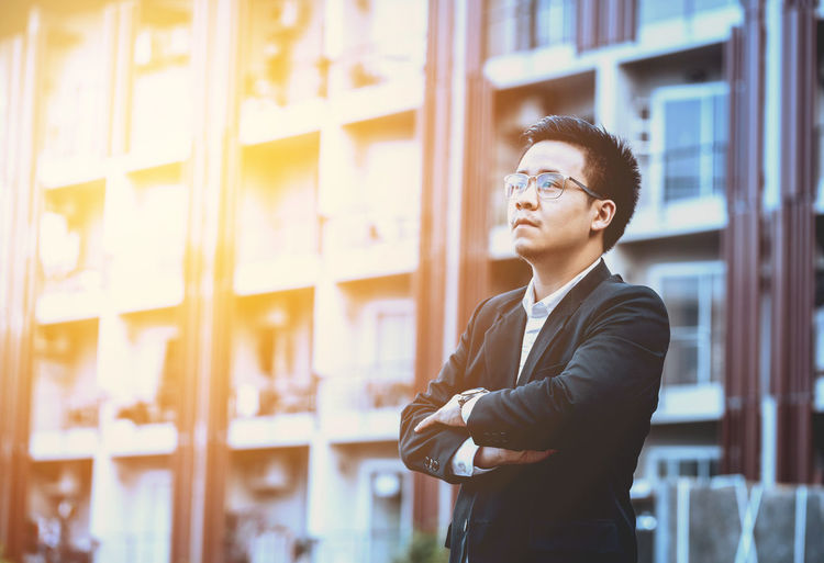 Confident young man standing against building