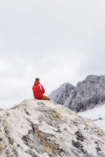 Person on rock in mountains against sky