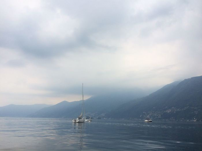 Cloudy Atmosphere Atmospheric Mood Beauty In Nature Boat Calm Cloud - Sky Day Mast Mode Of Transport Mountain Mountain Range Nature Nautical Vessel No People Non-urban Scene Sailboat Scenics Sea Sky Tranquil Scene Tranquility Transportation Vacations Water Waterfront