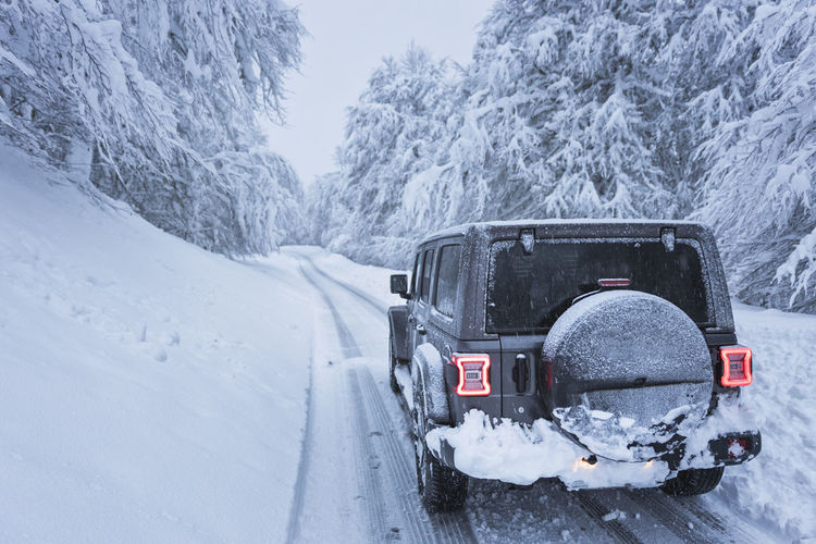 Snow covered car on snowcapped mountain