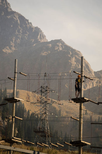 Man working on mountain against sky