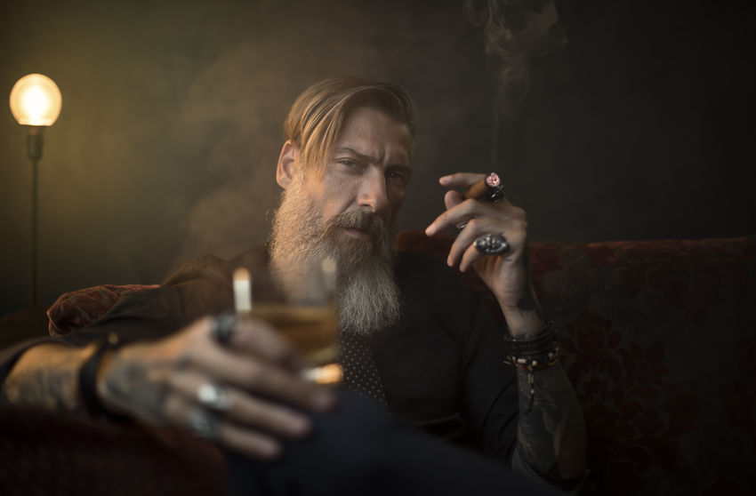 c65c5662d Portrait Of Man With Beard Smoking Cigar While Sitting On Sofa