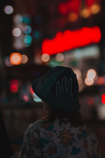 Rear view of girl standing in illuminated city at night