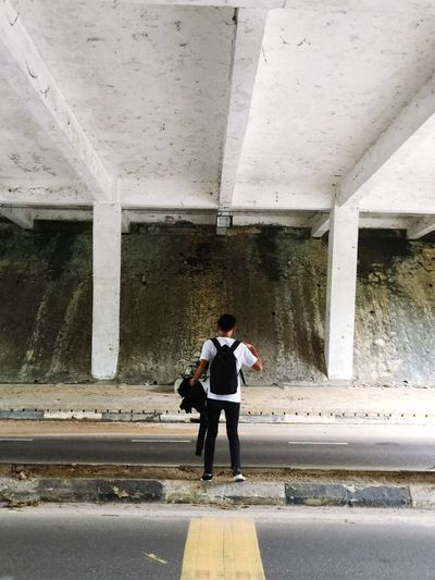 Rear view of man standing below bridge