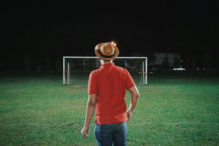 Rear view of man standing against goal post at night