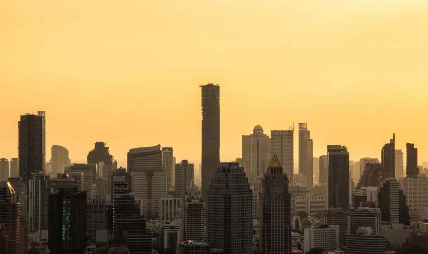 Skyscrapers in city against clear sky during sunset