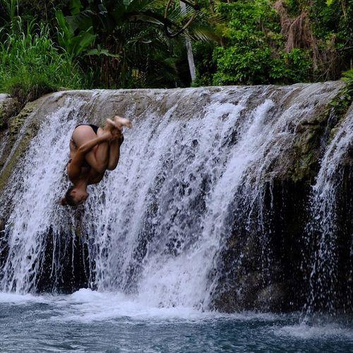 Man splashing water in waterfall