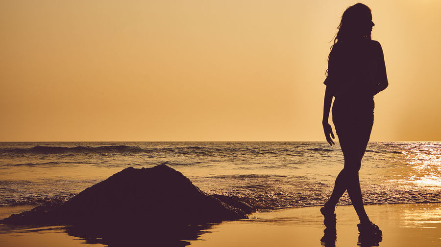 Silhouette woman walking at beach against clear sky during sunset