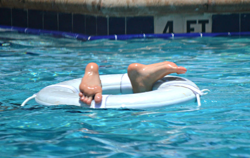 View of feet poking out of swimming pool