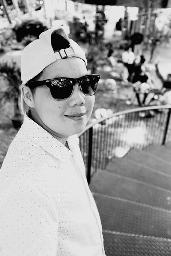 Portrait of woman wearing sunglasses while standing on staircase