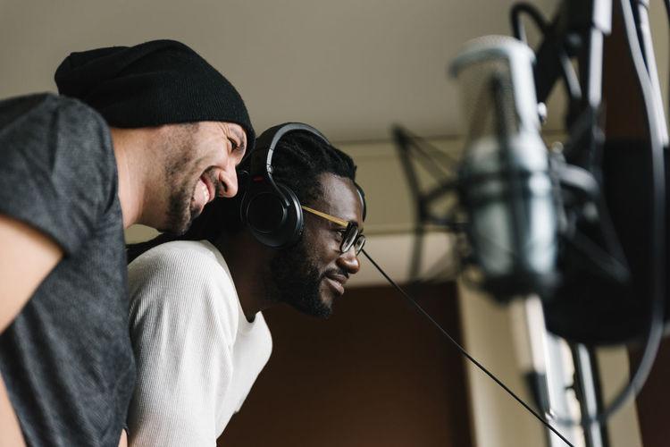 Men listening music while standing in studio