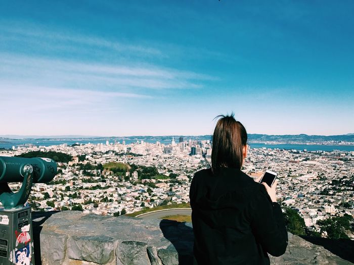 Rear view of woman looking at cityscape while standing at observation point against sky