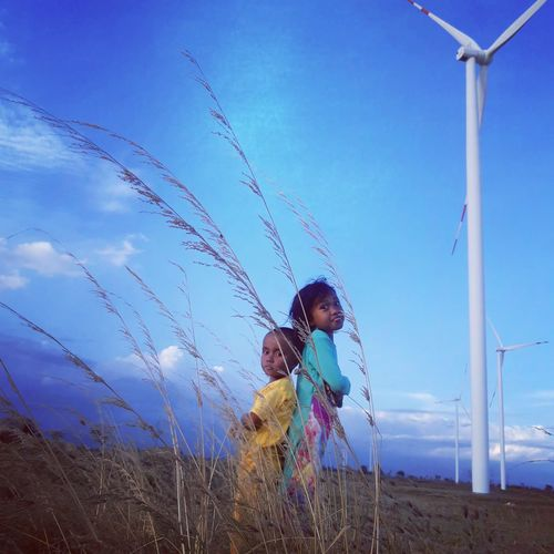 Cute kids standing by windmill against sky