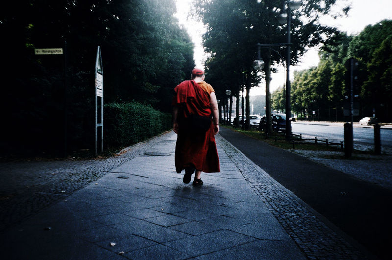 Full length rear view of monk walking at sidewalk in city