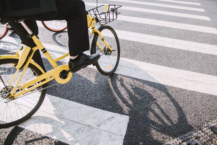 Low section of man with bicycle crossing on road