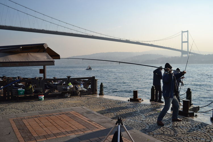 People fishing by river against bosphorus bridge during sunny day