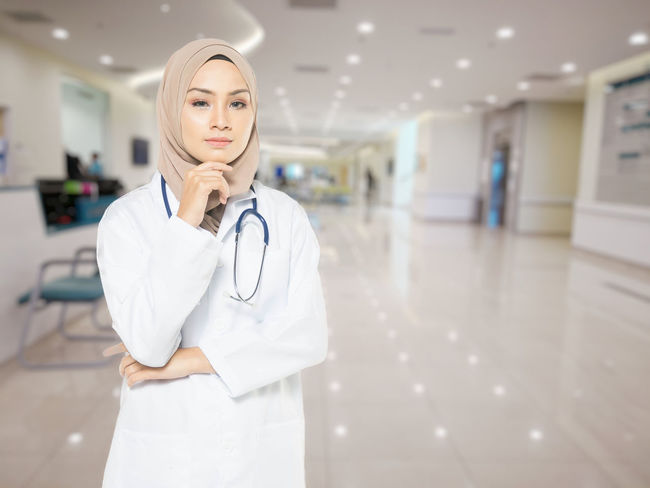 Adult Arcade Beautiful Woman Care Clothing Corridor Doctor  Female Doctor Focus On Foreground Front View Healthcare And Medicine Hospital Indoors  Lab Coat Medical Equipment Medical Instrument Medical Supplies Occupation One Person Responsibility Standing Stethoscope  Uniform Women