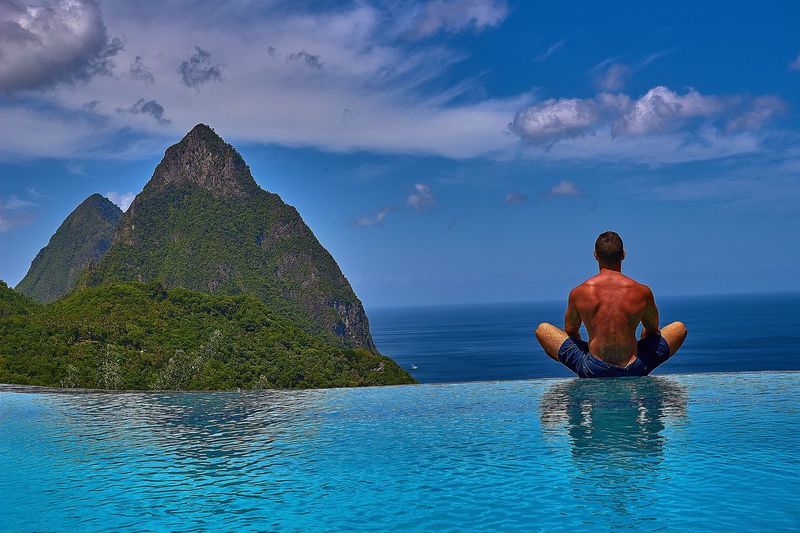 Rear view of shirtless man relaxing by infinity pool against sea