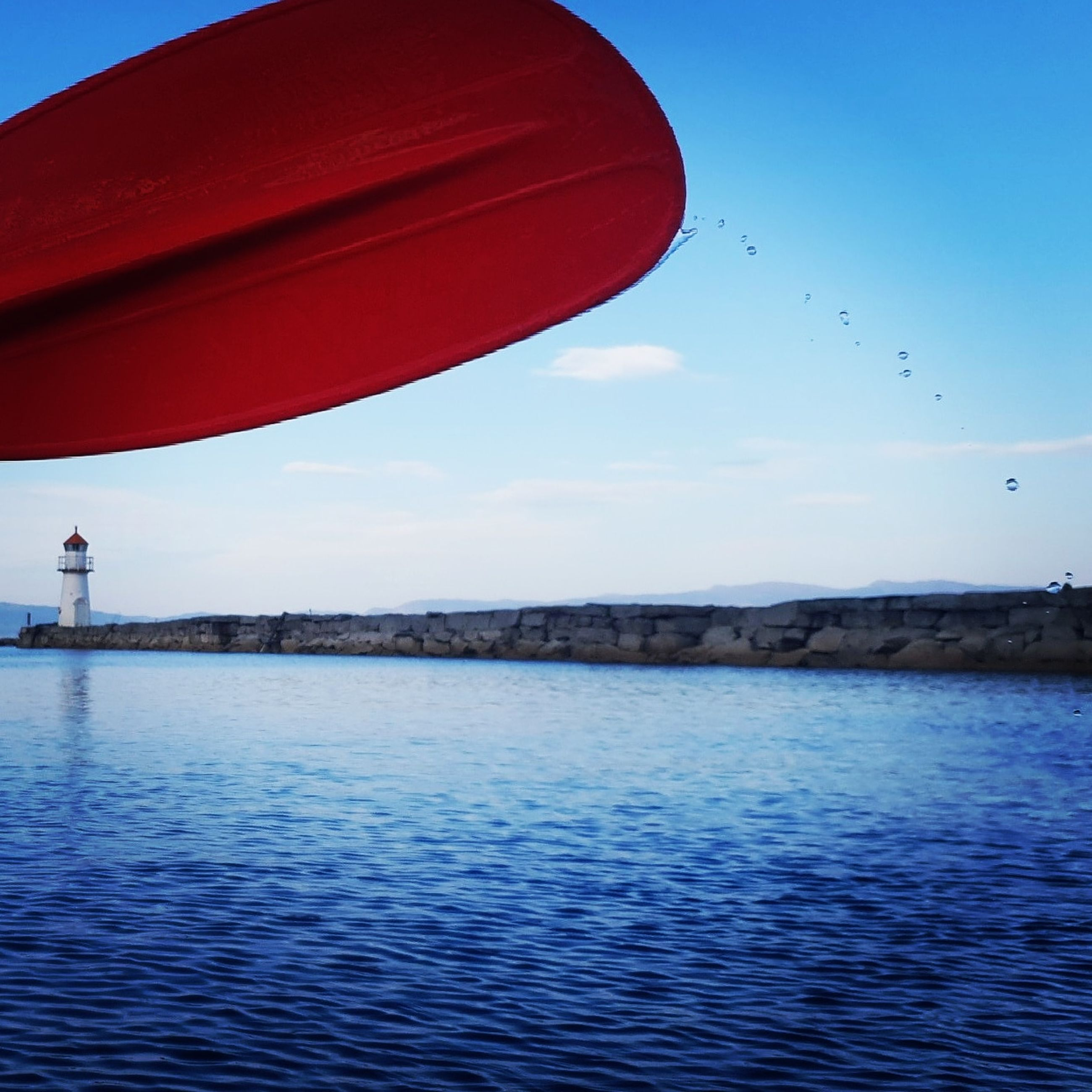 water, sky, waterfront, nature, sea, blue, flying, real people, day, scenics - nature, beauty in nature, one person, mid-air, leisure activity, outdoors, lifestyles, red, rippled